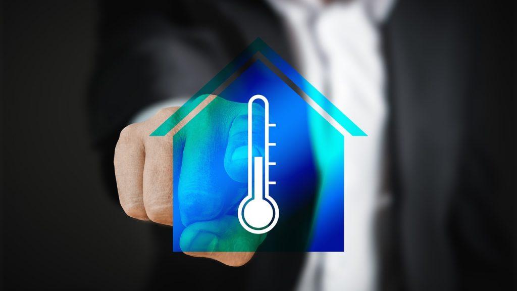 homme appuiyant sur l'icône représentant une maison bleu assortie d'un thermomètre à mercure, d'un écran tactile