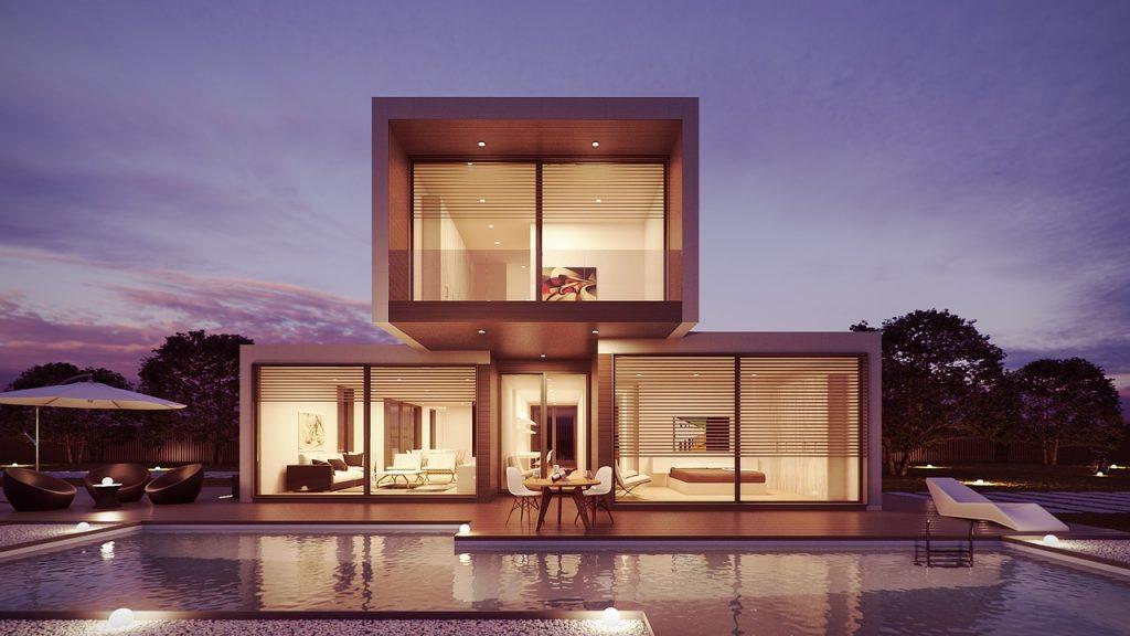 Vue d'une maison d'habitation contemporaine aux formes cubiques, assortie d'une piscine au premier plan
